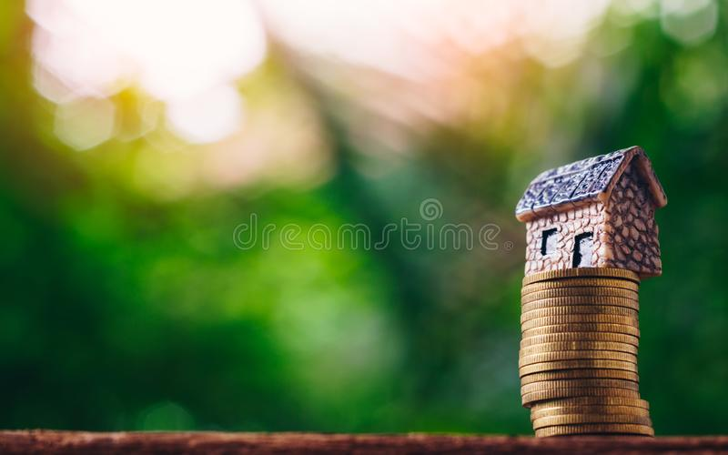 Coin money and house model on on green nature background. Concept for investment, saving, finance, banking, property ladder, mort royalty free stock image