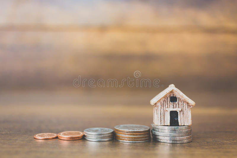 Coin money and house model on wooden background royalty free stock photography