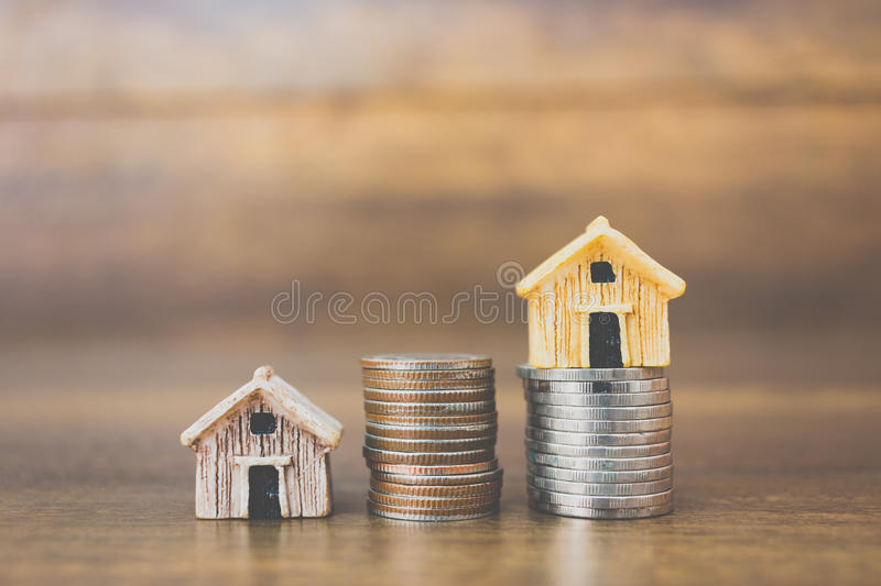 Coin money and house model on wooden background royalty free stock image