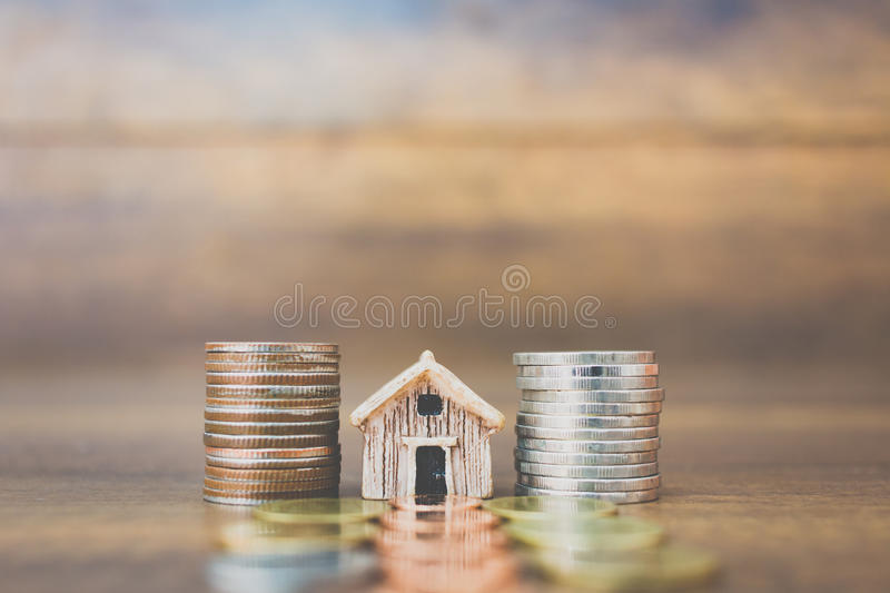 Coin money and house model on wooden background stock image