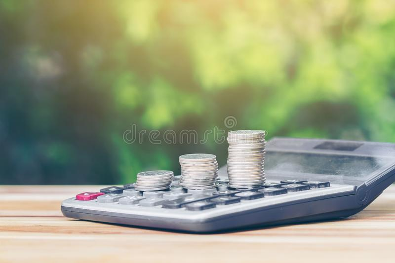 Coin is placed is on the calculator as a ladder. planning savings money of coins to buy a home. Concept for property ladder, mortgage, real estate, investment royalty free stock images