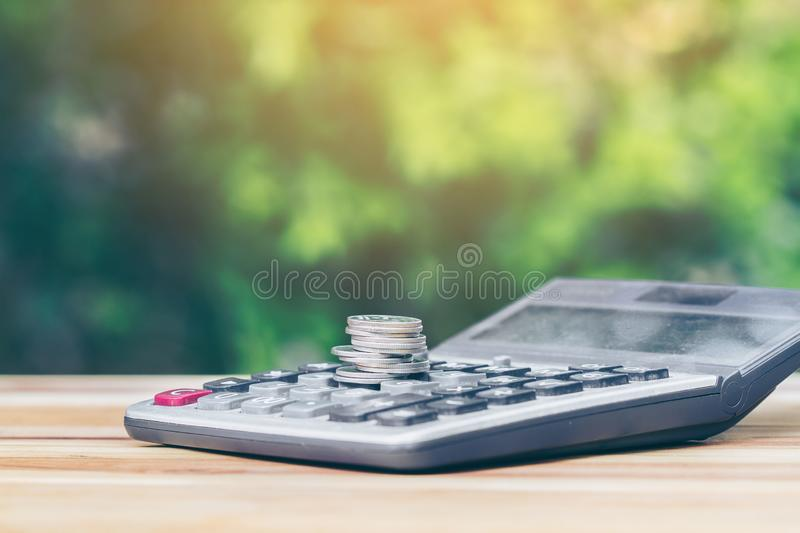 Coin is placed is on the calculator. Indicates business growth and savings. planning savings money of coins to buy a home. Concept for property, mortgage, real stock photography