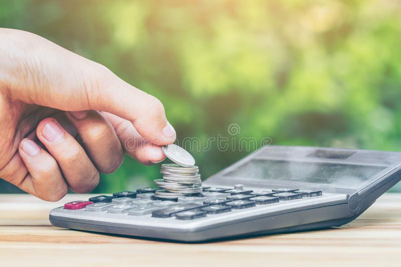 Coin is placed is on the calculator. man is placing is coin. planning savings money of coins to buy a home. Concept for property ladder, mortgage, real estate royalty free stock photography