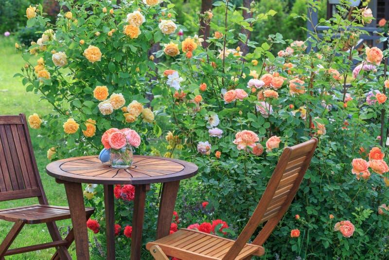 Coin salon romantique dans la roseraie, la table en bois ronde et les chaises près des grands buissons fleurissants des roses ang image libre de droits