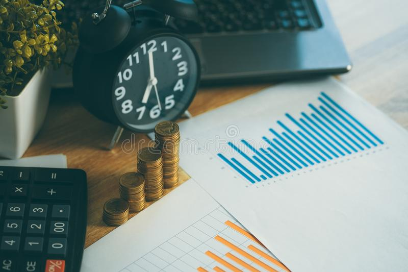 Coin stack and financial graph paper sheet with notebook calculator and alarm clock on working table for business concept stock images