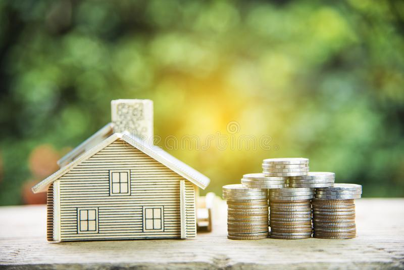 Coin stack with house model, savings plans for housing on green background. Coin stack with house model, savings plans for housing green background royalty free stock photos