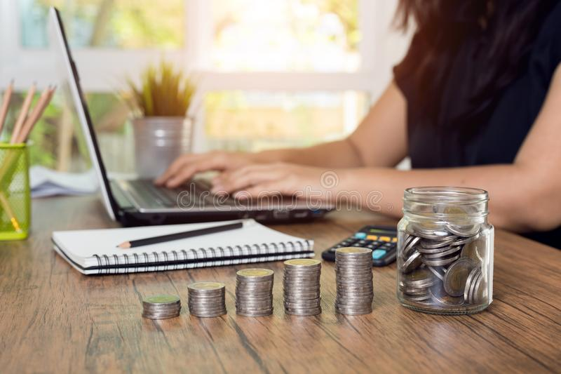 Coin stack step on desk with women using the computer. stock photo