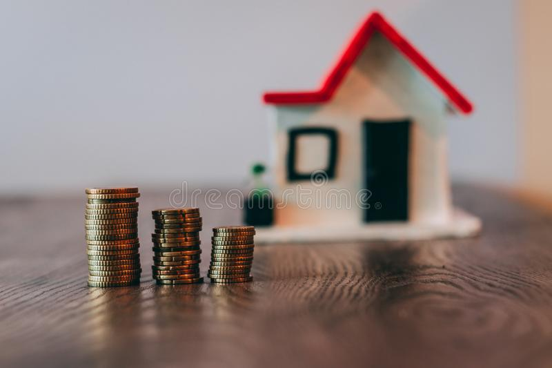 Coin stack on top of a wooden table, with a blurred house on the background: real estate, house mortgage, savings concept royalty free stock photo