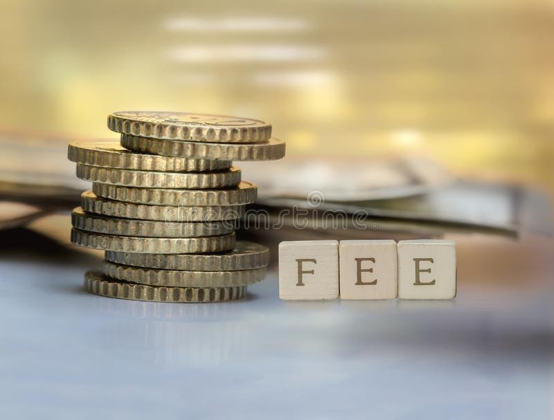 Coin stack and wooden blocks with the fee text. Fee Finance and Money concept royalty free stock image