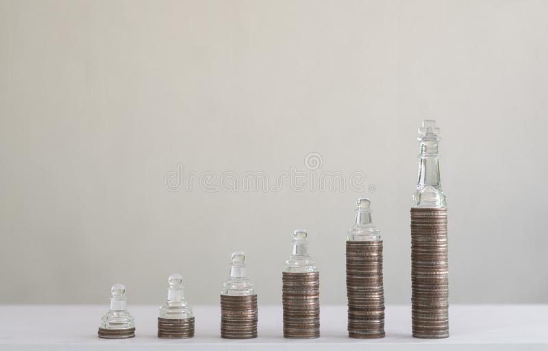 Coin stacks arranged into growth chart on white background, finance and business concept. Coin stacks arranged into growth chart with chess pieces on white royalty free stock image