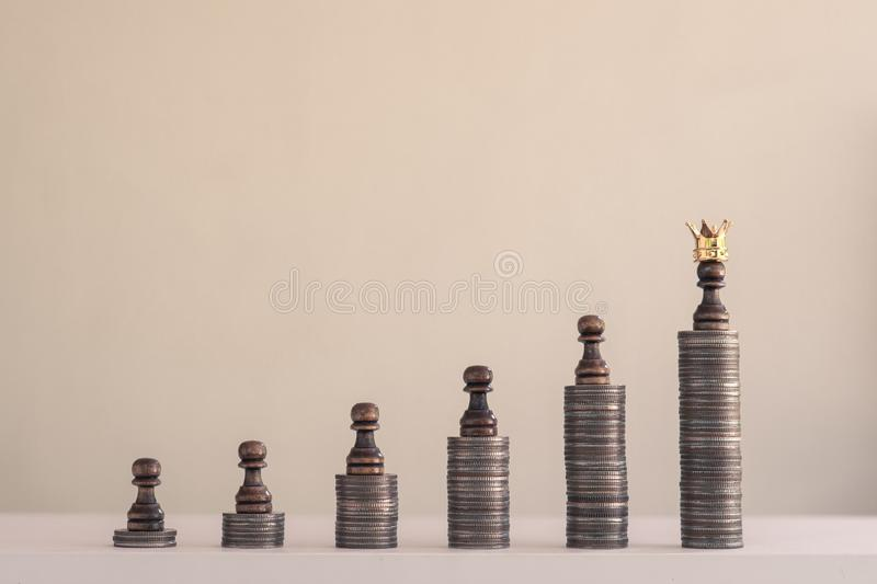Coin stacks arranged into growth chart on white background, finance and business concept. Coin stacks arranged into growth chart with chess pieces on white royalty free stock photos