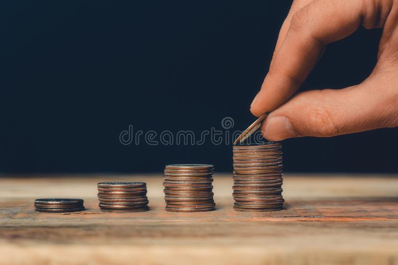 Coin stacks closeup with hand putting an US quarter on the top of the highest pile. Financial and business growth, economics,. Wealth, savings or banking stock images