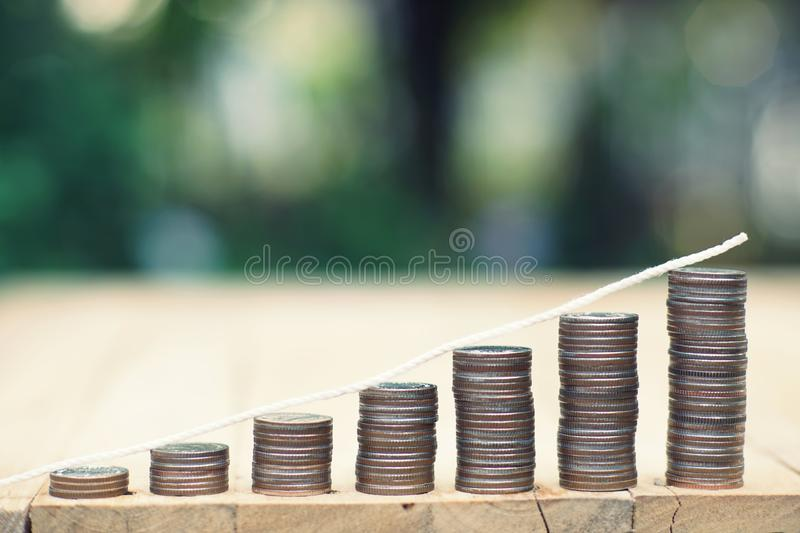 Coin stacks with trend curve on wooden table with blur green garden background, finance and business concept. Copy space vintage retro antique clock time royalty free stock image