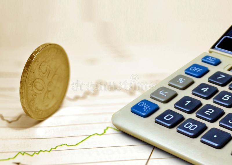 Coin on Stock Chart with Calculator. Image of Coin on Stock Chart with Calculator royalty free stock photos