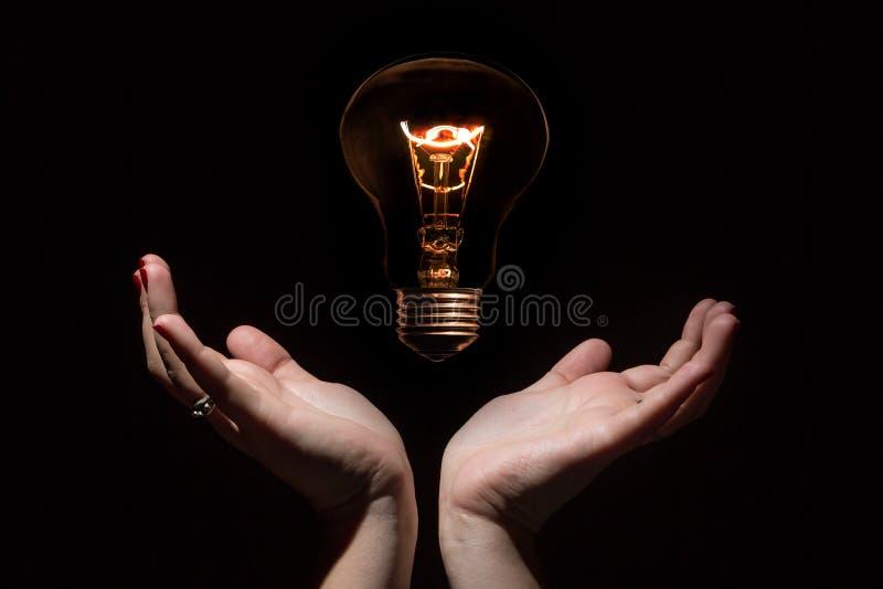 Coincept de la idea y del éxito Bombilla que brilla intensamente sin los alambres y las manos femeninas abiertas en fondo negro foto de archivo libre de regalías