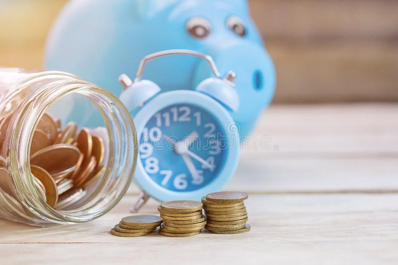 Coins,alram clock and piggy bank on wood table background. stock photography