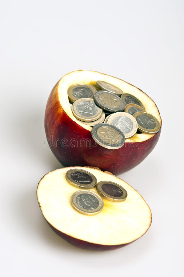 Coins on apple. Many coins inside red apple stock images