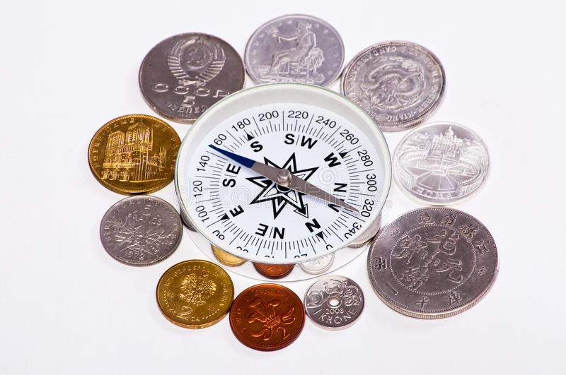 Coins around the compass. Coins of the world are around the compass royalty free stock image