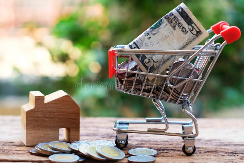 Coins and bank note in shopping cart with wooden house model aside. Property investment and home mortgage concept royalty free stock photo