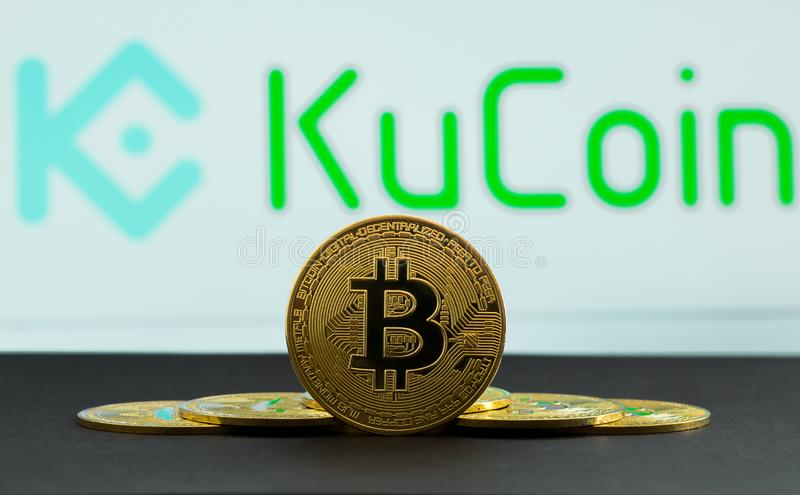 The coins of bitcoin are in front of logo of Ku Coin crypto stock exchange background. In the foreground is a BTC coins and on the stock photography