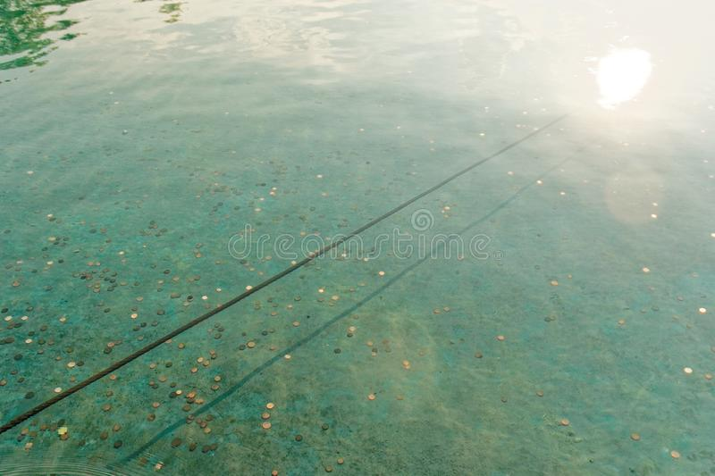 Coins at the bottom of a lake with blue water. royalty free stock photo