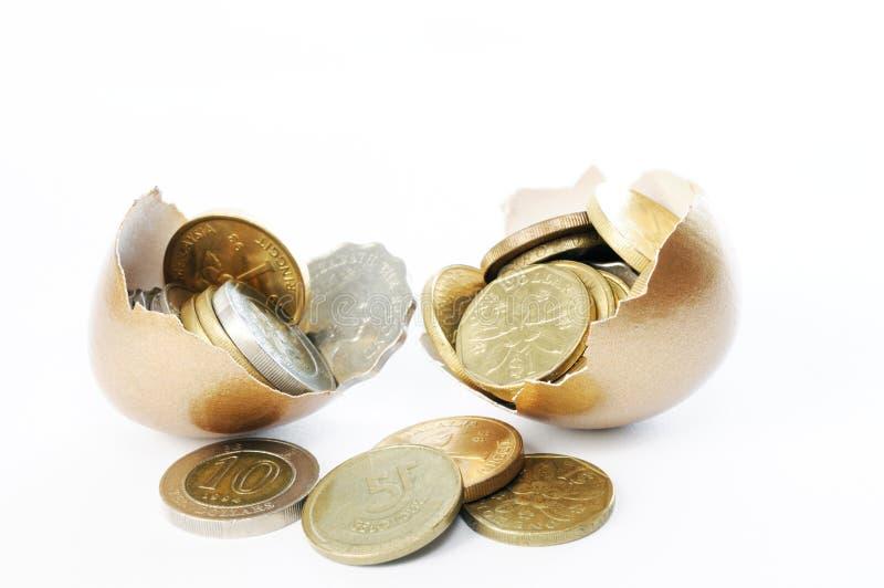 Coins in a broken golden eggshell stock photography