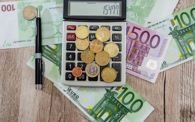 Coins on a calculator, euro and pen on the table. View from above. stock photography