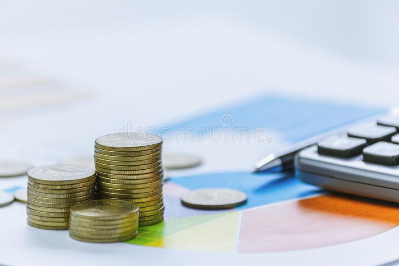 Coins, calculator, pen and graph on table accounting business or financial concept royalty free stock photography