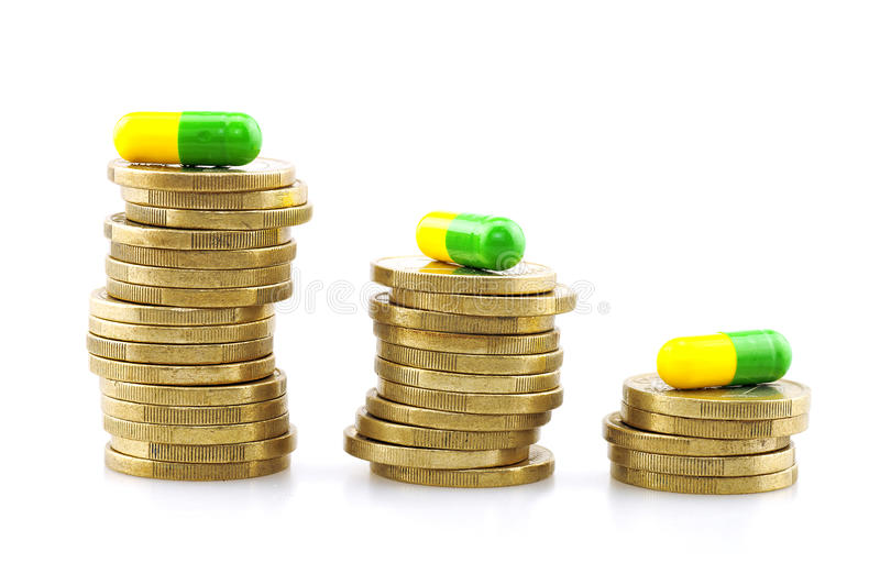Coins and capsules, medical expenses royalty free stock image