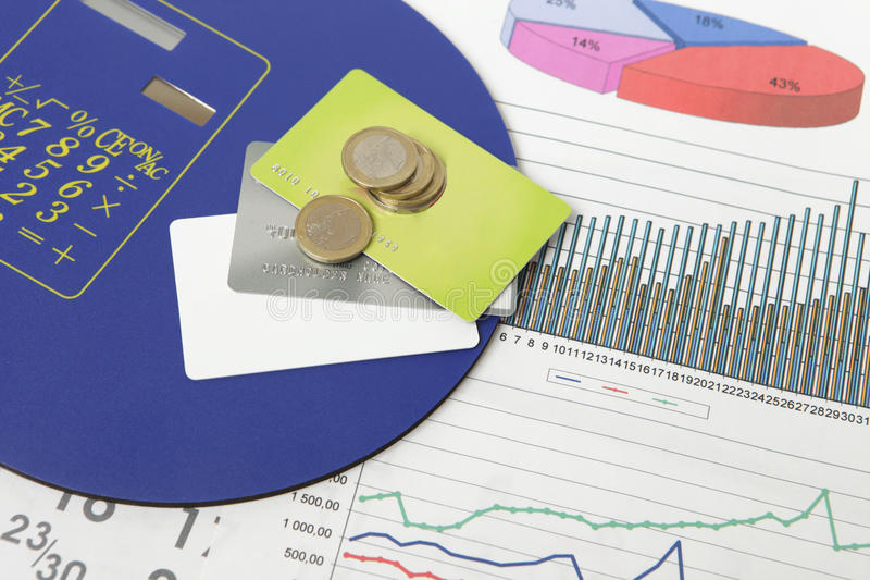 Coins and credit cards on a document with some graphics stock images