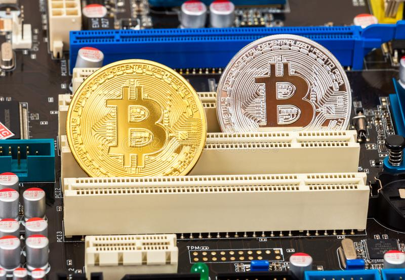 Coins of Cryptocurrency Bitcoin lying over electronic computer c royalty free stock photography