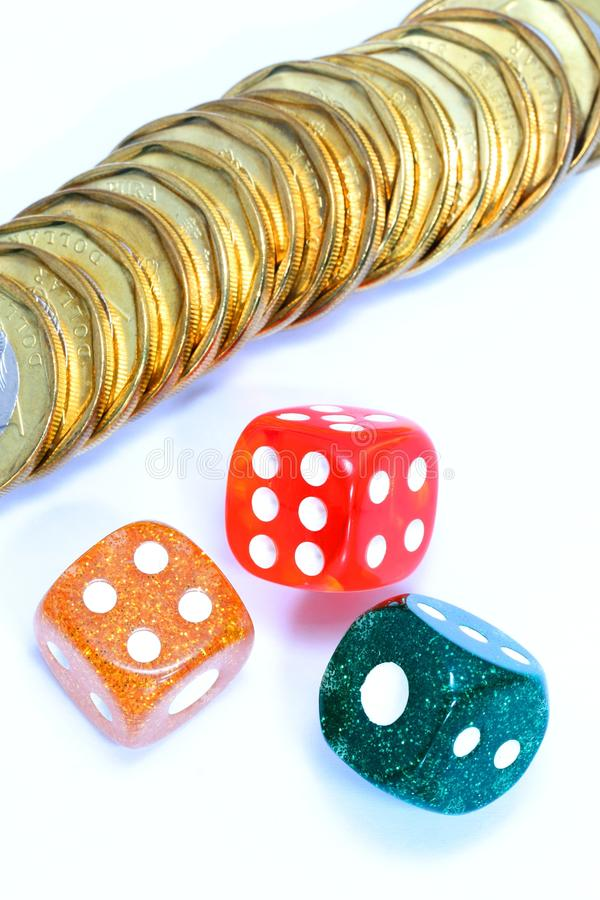 Coins and dices. Conceptual Image with a variety of uses in any area where the coins and dices may be stacked against you.... investments, gambling, banking royalty free stock images