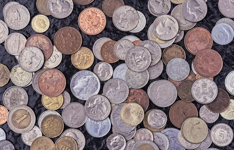 Coins of different countries of the world. A collection of old and modern coins. Background from metal coins royalty free stock image