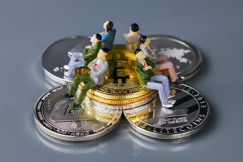 Coins of different crypto-currencies with the people sitting on them. royalty free stock images
