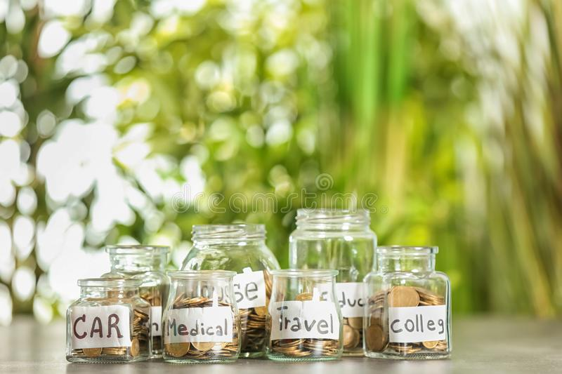 Coins for different needs in glass jars on table outdoors. Money savings concept royalty free stock photo