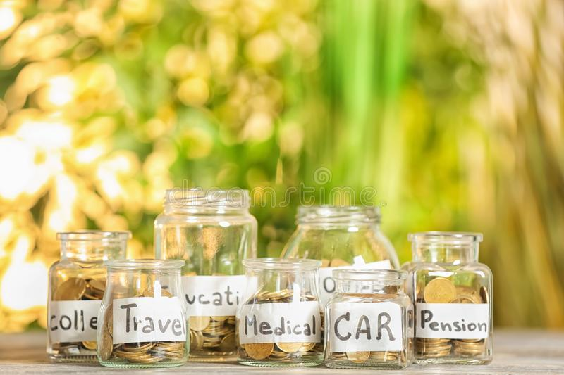 Coins for different needs in glass jars on table outdoors. Money savings concept stock photography