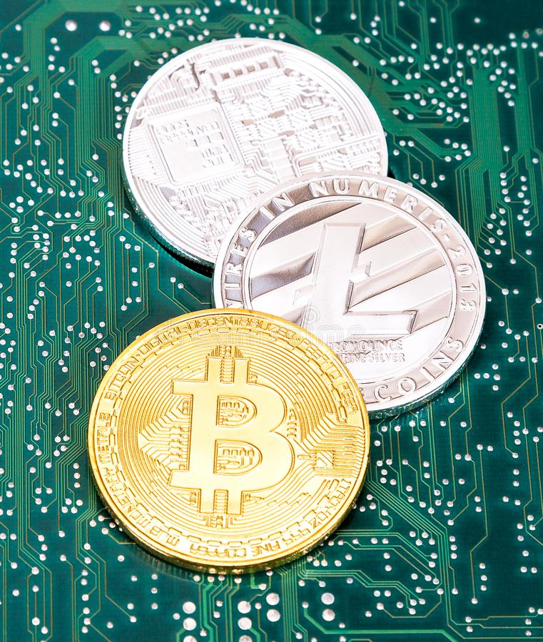 Coins of digital cryptocurrency lying over electronic computer c stock photos