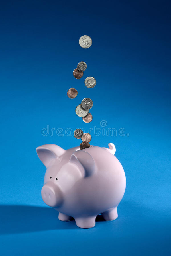 Coins dropping into a piggy bank royalty free stock images