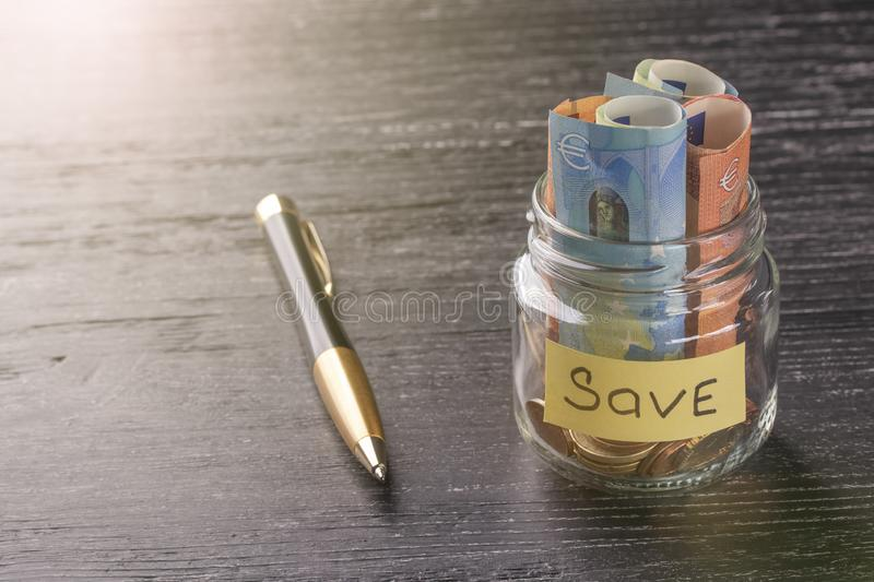 Coins and Euro notes in a glass jar and pen on a black wooden table royalty free stock images