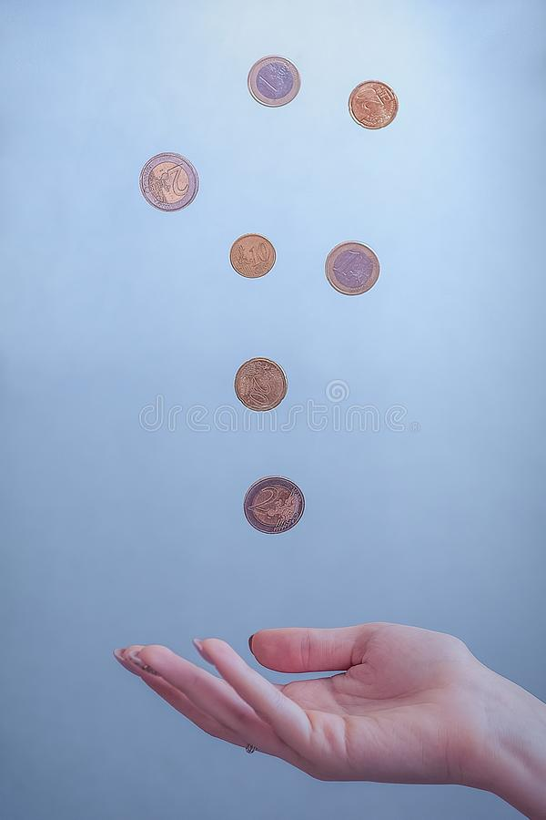 Coins fall on blue background royalty free stock image