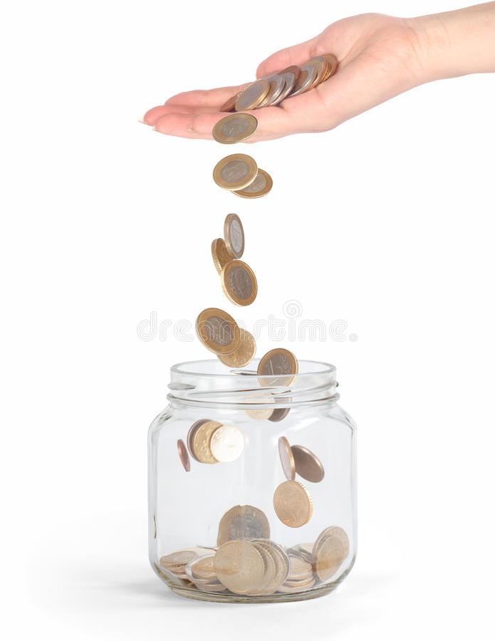 Coins falling into the glass jar from hand. Isolated royalty free stock image
