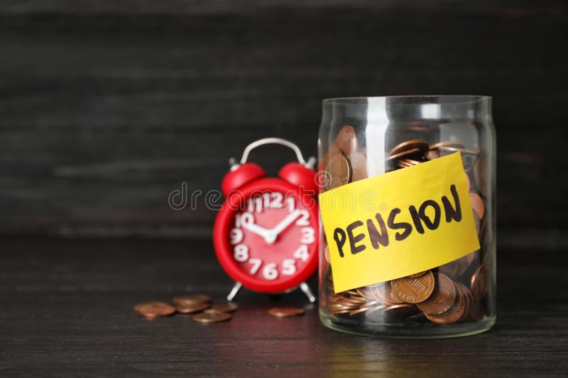 Coins in glass jar with label `PENSION` stock photos