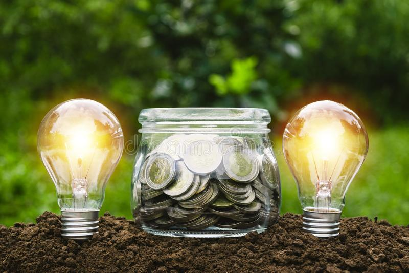Coins in glass jar with light bulbs young plant on top put on th royalty free stock photos