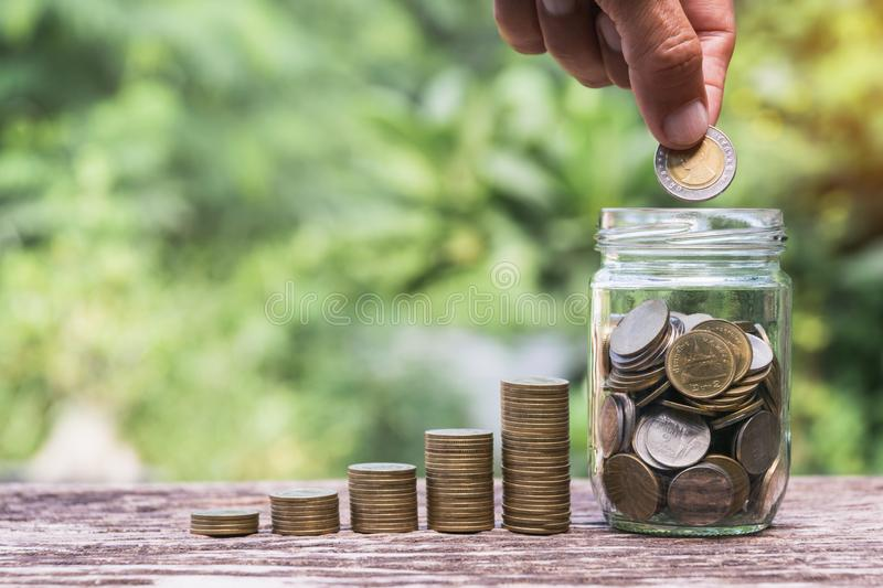 Coins in glass jar  Set on wooden plate, put in a green park background also some coins beside.  stock images