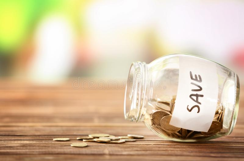 Coins in glass jar with text SAVE on table against blurred background. Concept of savings royalty free stock image