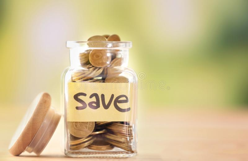Coins in glass jar with text SAVE on table against blurred background. Concept of savings stock image