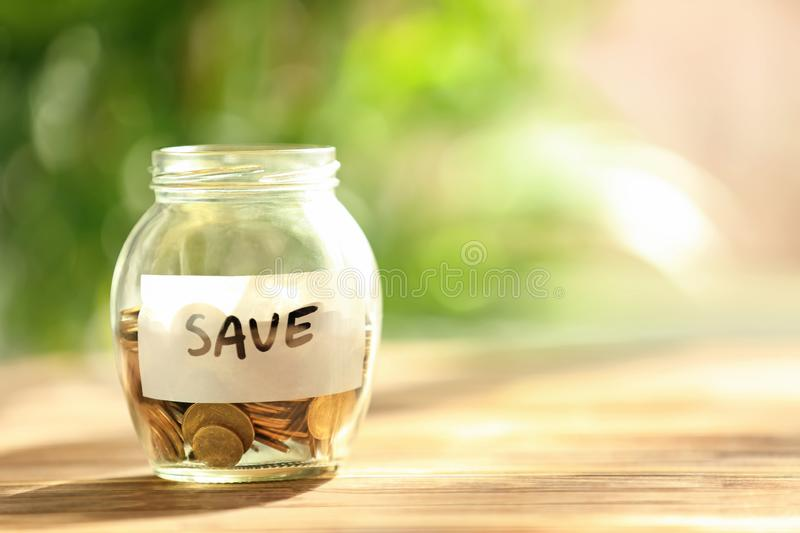 Coins in glass jar with text SAVE on table against blurred background. Concept of savings stock images