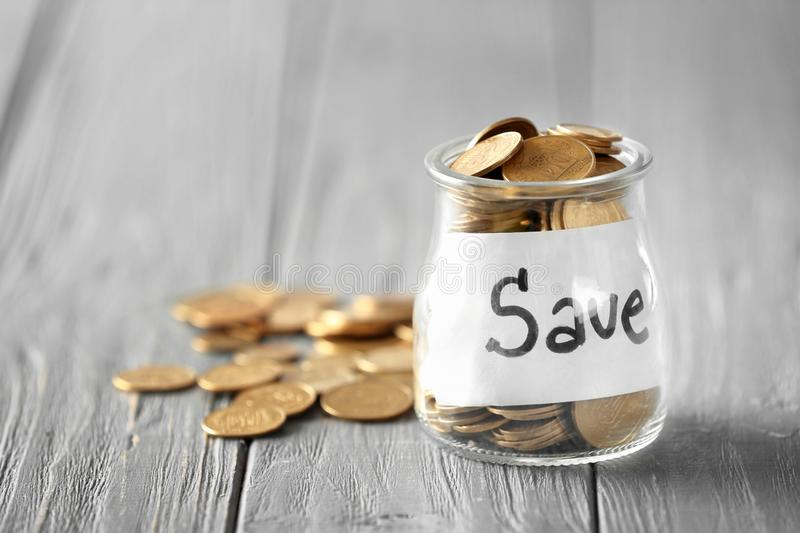 Coins in glass jar with text SAVE on table. Concept of savings royalty free stock photo