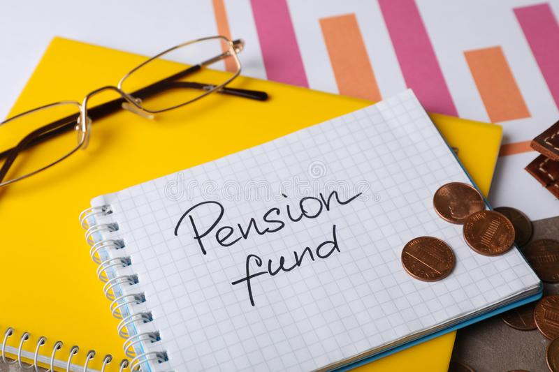 Coins, glasses and notebook with words PENSION FUND. On table royalty free stock photo