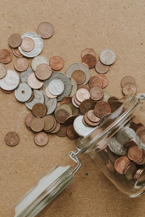 Coins going out from a dropped glass jar over a wooden table. Vi. Ntage tone stock image